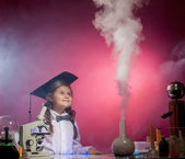 Attentive girl watches evaporation of reagents — Stock Photo
