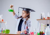 Serious chemist looking at reagent in flask — Stock Photo