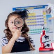 Stock Photo: Cute dark-haired girl looking through magnifier