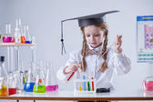 Image of smart girl mixing tubes in laboratory — Stock Photo