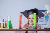 Smiling little chemist posing with colorful flasks — Foto de Stock