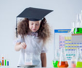 Cute curly-haired scientist stirs reagent in flask — Stock Photo