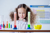 Slyly smiling girl posing with colorful test-tubes — Stock Photo