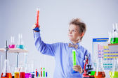 Handsome school boy posing with test-tubes in lab — Stock Photo