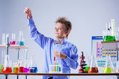 Cute boy posing with variety of reagents in lab — Stock Photo
