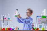 Funny smiling boy holding flask with reagent — Stok fotoğraf