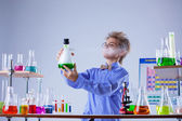 Inquisitive boy looking for evaporation of reagent — Foto de Stock