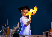 Image of witted boy holding fire in his hands — Stock Photo
