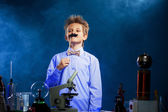 Cute school boy posing with fake mustache in lab — Stock Photo
