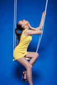 Sensual young model with UV makeup posing on swing — Stockfoto