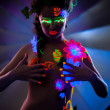 Stock Photo: Naked womwith makeup, glowing under UV light