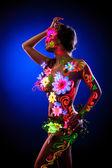 Modelo sexy, posando com flores brilhantes - luz uv — Foto Stock