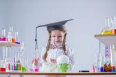 Curious schoolgirl conducting experiment in lab — ストック写真