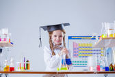 Smiling little girl posing in graduate hat at lab — Stock Photo
