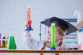 Interested schoolgirl considering colorful flasks — Stock Photo
