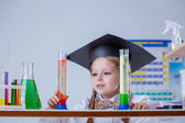 Beautiful little pupil posing with test tubes — Stock Photo