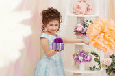 Cute girl posing with gift box in decorated studio — Stock Photo