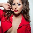 Hot curly brunette posing topless in red jacket — Stock Photo