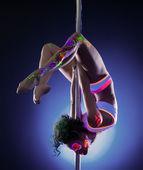 Pretty girl posing hanging upside down on pylon — Stock Photo