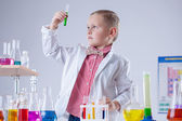 Cute boy looking at color of reagent in test-tube — Stock Photo