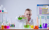 Funny young chemist pouring reagent into flask — Stock Photo