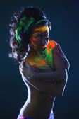 Topless girl posing with glowing UV makeup — Stock Photo