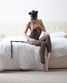Playful catwoman posing in hotel room — Stock Photo