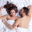 Pair of handsome young lovers lying on silk sheets — Stock Photo #45693515