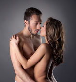 Passionate nude lovers embracing in studio — Foto Stock
