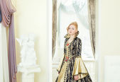 Charming young woman posing in deluxe king costume — Stock Photo