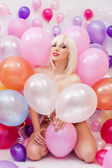Sexy platinum blonde posing with balloons — Stock Photo