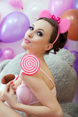Cute young woman posing with pink lollipop — Stock Photo
