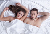 Image of young heterosexual couple posing in bed — Stock Photo