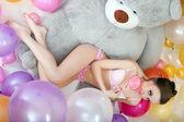 Playful model lying with lollipop on teddy bear — Stock Photo