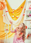 Beautiful curly-haired girl plays with petals — Stock Photo