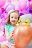 Cheerful girl playfully put crown on balloon — Stock Photo