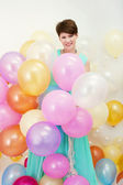 Pretty woman holds big bunch of colorful balloons — Stock Photo