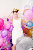 Cheerful adult woman tries on toy crown — Stock Photo