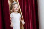 Image of lovely little girl looking out curtains — Stock Photo