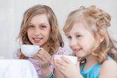 Studio shot van gelukkig weinig meisjes het drinken van thee — Stockfoto
