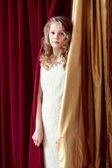 Charming curly girl posing on curtains background — Stock Photo