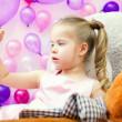 Funny little girl attentively looks on lollipop — Stock Photo #48396367