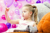 Funny little girl attentively looks on lollipop — Stock Photo