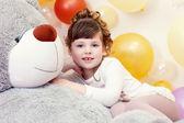 Adorable niña posando recostada oso de peluche — Foto de Stock