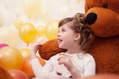 Joyful little girl posing hugging plush bear — Stock Photo