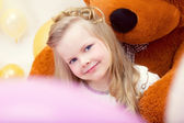 Smiling blue-eyed girl posing with teddy bear — Stock Photo