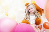 Smiling blonde girl playing with teddy bear — Stockfoto