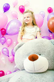 Smiling little girl posing with plush bear — Stock Photo