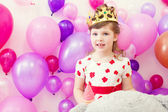 Cute girl posing in crown on balloons background — Stockfoto