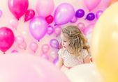 Pretty girl posing in studio where lot of balloons — Stock Photo